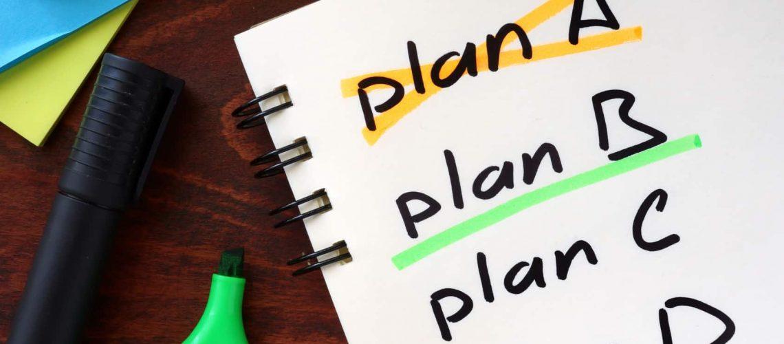 Cross plan A, underline plan B concept  written in a notebook on a wooden table.