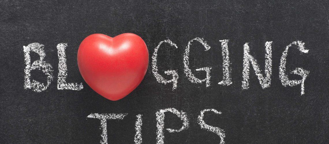 blogging tips phrase handwritten on blackboard with heart symbol instead of O